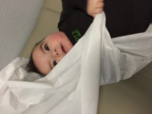He was on the exam table for 30 seconds waiting for the doctor. In that time he grabbed the paper with both hands and tried to wrap it around himself.